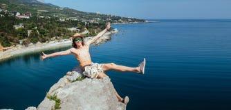 玻璃和帽子的年轻愉快的微笑的人坐岩石的边缘 图库摄影