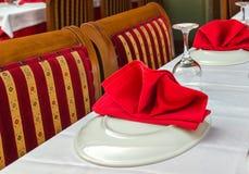 玻璃和板材在饭桌上在餐馆 免版税库存照片