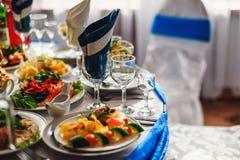 玻璃和板材用食物在桌上在餐馆 图库摄影
