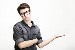 玻璃和牛仔裤衬衣指向的年轻英俊的人去,当站立反对白色背景时 库存图片