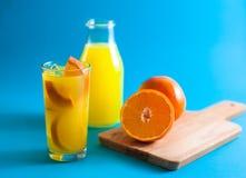玻璃和瓶与半和整个新orang的橙汁 免版税库存图片