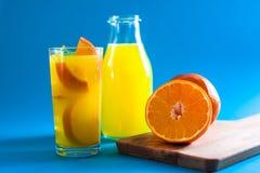 玻璃和瓶与半和整个新orang的橙汁 免版税图库摄影