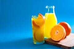 玻璃和瓶与半和整个新orang的橙汁 免版税库存照片