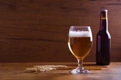 玻璃和瓶啤酒,大麦的耳朵在木桌上的 侥幸 免版税图库摄影