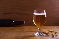 玻璃和瓶啤酒,大麦的耳朵在木桌上的 侥幸 库存图片