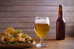 玻璃和瓶啤酒,大麦的耳朵在木桌上的 侥幸 免版税库存照片