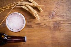 玻璃和瓶啤酒,大麦的耳朵在木背景的 侥幸 免版税库存照片
