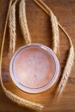 玻璃和瓶啤酒,大麦的耳朵在木背景的 侥幸 图库摄影