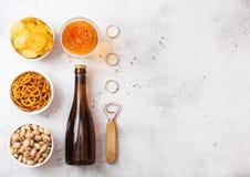 玻璃和瓶工艺与快餐和开启者的储藏啤酒在石厨房用桌背景 椒盐脆饼和油炸马铃薯片和开心果 库存照片