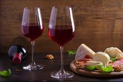 玻璃和瓶酒用乳酪、面包、坚果和jamon或者熏火腿在黑暗的木背景 免版税图库摄影