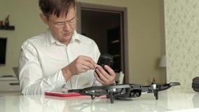 玻璃和白色衬衫的成熟人装配一quadrocopter,连接控制,学会的概念 股票录像