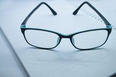 玻璃和笔记本 免版税库存图片