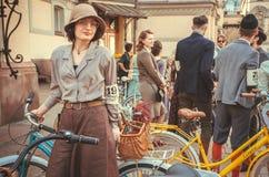 玻璃和老式礼服的妇女在自行车节日减速火箭的巡航的人群等待的开始 免版税库存图片