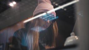 玻璃工作的一名时髦的行家妇女与膝上型计算机 底视图通过窗口 免版税库存照片