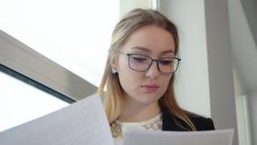 玻璃工作的年轻被集中的女实业家与纸张文件 股票录像
