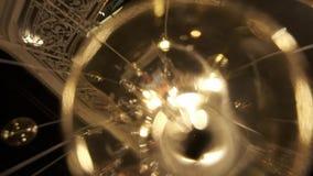 玻璃昂贵的大枝形吊灯在餐馆或音乐堂 枝形吊灯照明设备在霍尔, Bokeh,强光,焕发 股票视频