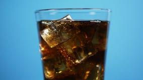 玻璃有很多与冰块的可乐泡沫腾涌的饮料 冷的焦炭闪耀的苏打蓝色 股票录像