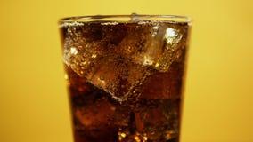 玻璃有很多与冰块的可乐泡沫腾涌的饮料 冷的焦炭闪耀的苏打黄色 股票录像