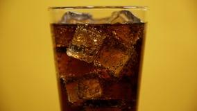 玻璃有很多可乐泡沫腾涌的饮料冰块 冷的闪耀的苏打黄色背景 股票录像