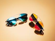 玻璃有的一些副精华太阳镜在金背景的五颜六色的透镜 免版税库存图片