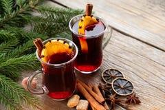 玻璃杯子与香料和圣诞树分支的加香料的热葡萄酒在桌上 复制文本的空间 免版税库存图片