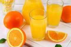 玻璃杯子和一个投手与切片的新鲜的橙汁在一张浅灰色的桌上的橙色和黄色管 库存照片