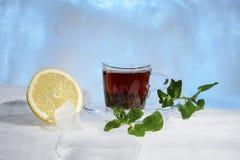 玻璃杯子在美丽的蓝色冰的强的红茶用黄色柠檬和绿色薄菏 免版税库存照片
