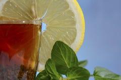 玻璃杯子在美好的蓝色背景的强的红茶用一个黄色柠檬和绿色薄菏 库存图片