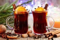 玻璃杯子热的加香料的热葡萄酒,圣诞树分支和bokeh光在背景 免版税图库摄影