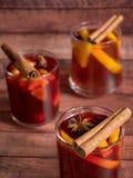 玻璃杯红葡萄酒仔细考虑了在木背景的酒用桂香香料和桔子 选择聚焦 图库摄影