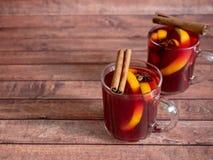 玻璃杯红葡萄酒仔细考虑了在木背景的酒用桂香香料和桔子 选择聚焦 免版税库存照片