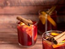 玻璃杯红葡萄酒仔细考虑了在木背景的酒用桂香香料和桔子 选择聚焦 免版税图库摄影