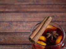 玻璃杯红葡萄酒仔细考虑了在木背景的酒用桂香香料和桔子 选择聚焦 免版税库存图片