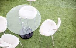 玻璃桌和白色椅子顶视图在绿色背景 库存照片
