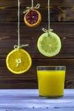 玻璃水瓶柑橘饮料冰橙色夏天水 垂悬在螺纹切片柠檬、桔子和石灰 新鲜的夏天,杯橙汁 免版税库存照片