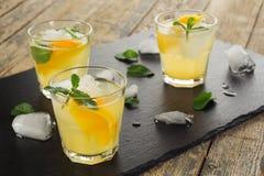 玻璃水瓶柑橘饮料冰橙色夏天水 柑橘柠檬水用薄菏和冰在白色木背景 库存照片