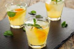 玻璃水瓶柑橘饮料冰橙色夏天水 柑橘柠檬水用薄菏和冰在白色木背景 免版税图库摄影