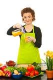 玻璃汁液橙色倾吐的妇女 库存照片