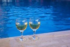 玻璃游泳池边二酒 免版税库存照片