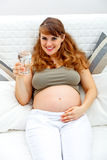 玻璃现有量怀孕的微笑的水妇女 免版税库存图片