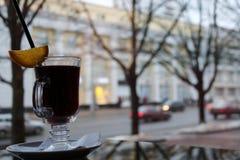 玻璃玻璃用在一张桌上的棕色,鲜美,热,芬芳,酒精,温暖的被仔细考虑的酒在一个咖啡馆在反对窗口的晚上 免版税图库摄影