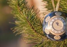 玻璃球,与一个时钟的圣诞节装饰在树 库存图片