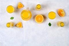 玻璃瓶、玻璃和一个投手与切片的新鲜的橙汁在一张浅灰色的桌上的橙色和黄色管 顶视图 免版税库存图片