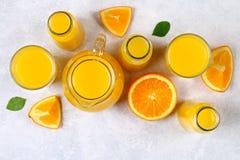 玻璃瓶、玻璃和一个投手与切片的新鲜的橙汁在一张浅灰色的桌上的橙色和黄色管 顶视图 免版税库存照片