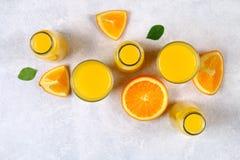 玻璃瓶、玻璃和一个投手与切片的新鲜的橙汁在一张浅灰色的桌上的橙色和黄色管 顶视图 库存图片