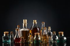 玻璃瓶不同的形状和大小充满不同颜色液体在黑背景的 免版税库存图片