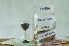 玻璃瓶子以充分与标记的硬币作为挽救,投资, 免版税库存照片