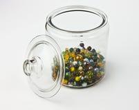 玻璃瓶子半满五颜六色的玻璃大理石 免版税库存照片