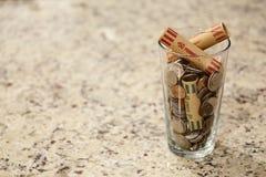 玻璃瓶子在杯子的硬币在工作台面书桌金钱储款债务银行富有的恶劣的美元财务财富变动市场现金 图库摄影