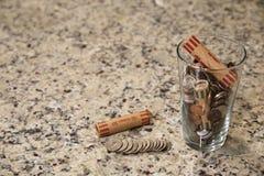 玻璃瓶子在杯子的硬币在工作台面书桌金钱储款债务银行富有的恶劣的美元财务财富变动市场现金 库存图片